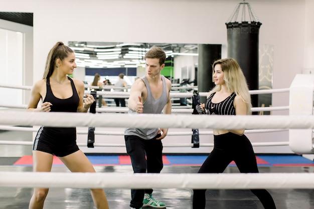 2人のボクサーの女性が戦いの前にお互いに挨拶し、若いハンサムなトレーナーがその間に立っています。ボクシングの人々