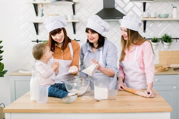 祖母、2人の娘、台所で焼く小さな女の赤ちゃん連れのご家族。祖母は生地に砂糖を追加します。母の日のコンセプト、家族のベーキング