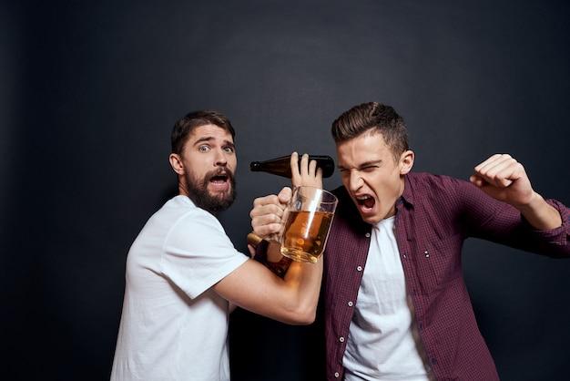 2人の男性が楽しみ、ビールを飲み、ファーストフードを食べます。