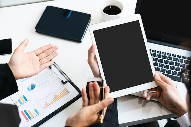 2人の同僚がオフィスの机のテーブルにタブレットでデータを議論します。ビジネスチームの分析と戦略の概念を閉じます。