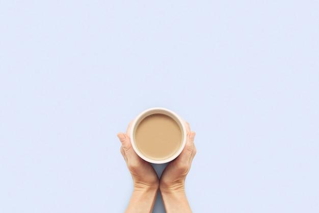 青色の背景にホットコーヒーとカップを保持している2つの手。コーヒーまたは紅茶の朝食のコンセプトです。おはよう、夜、不眠症。フラット横たわっていた、トップビュー