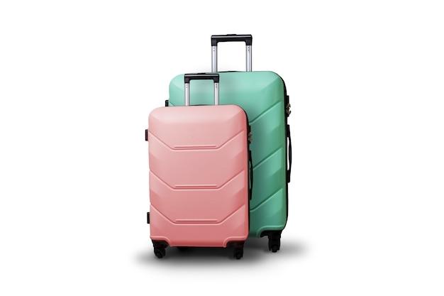 孤立した白地に車輪の上の2つのスーツケース。旅行、休暇旅行、親戚への訪問の概念。ピンクとグリーンの色
