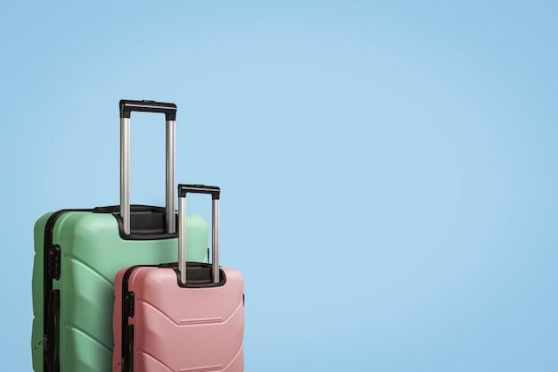 青色の背景に車輪の上の2つのスーツケース。旅行、休暇旅行、親戚への訪問の概念。ピンクとグリーンの色
