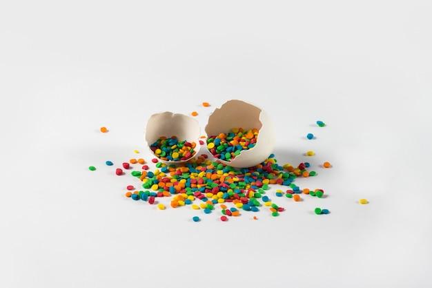 イースターのコンセプト。白い表面に2つの壊れた卵卵殻とイースター甘い多色の装飾品