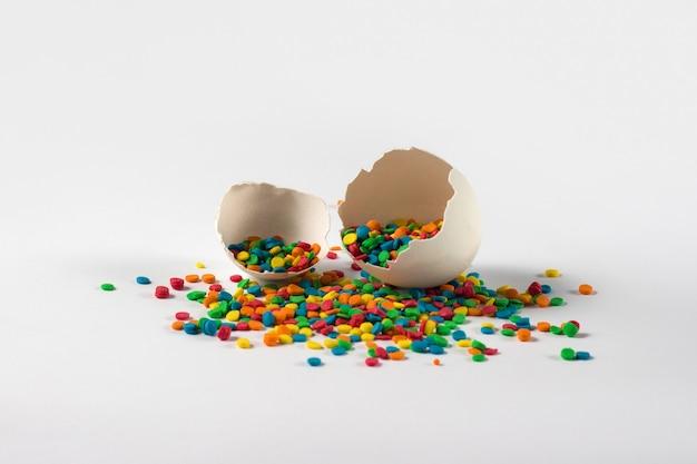 2つの壊れた卵とイースターのカラフルな装飾は、白い表面のシェルから注ぐ。イースターのコンセプト