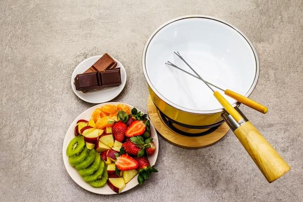 チョコフォンデュ。新鮮なフルーツの盛り合わせ、2種類のチョコレート。甘いロマンチックなデザートを料理するための材料。
