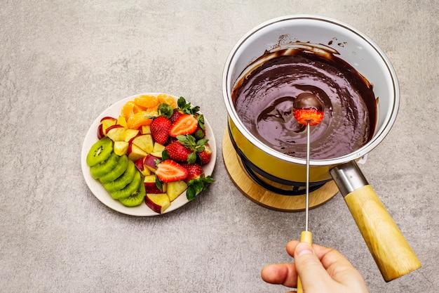 チョコフォンデュ。新鮮なフルーツの盛り合わせ、2種類のチョコレート、男性の手。甘いロマンチックなデザートを料理するための材料。