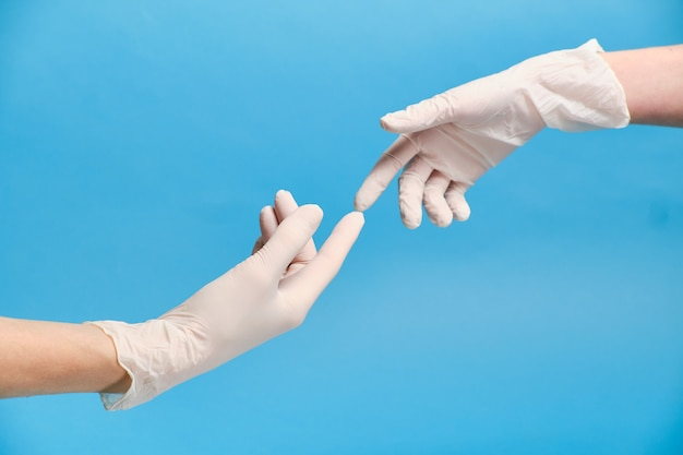 パンデミックコロナウイルスの検疫中に、手袋をした2つの手が互いに接触します。保護されたセックスの概念。検疫の概念。