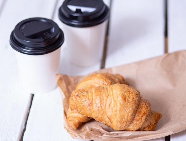紙コップと白い木製のテーブルのクロワッサンで2つのコーヒー