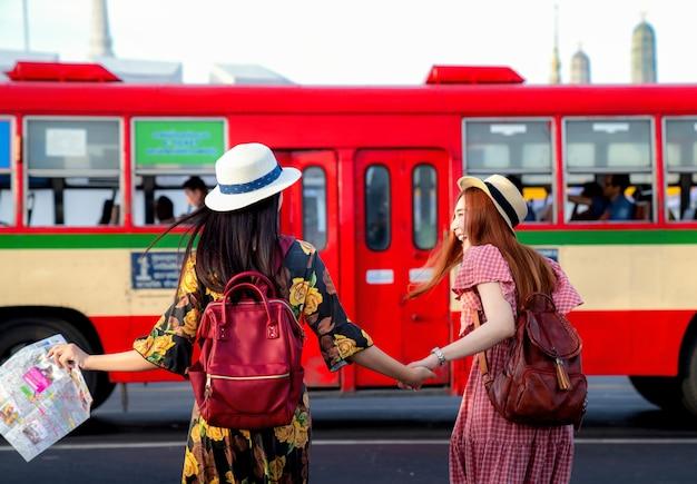 2つのアジアのガールフレンド旅行とバスでの交通