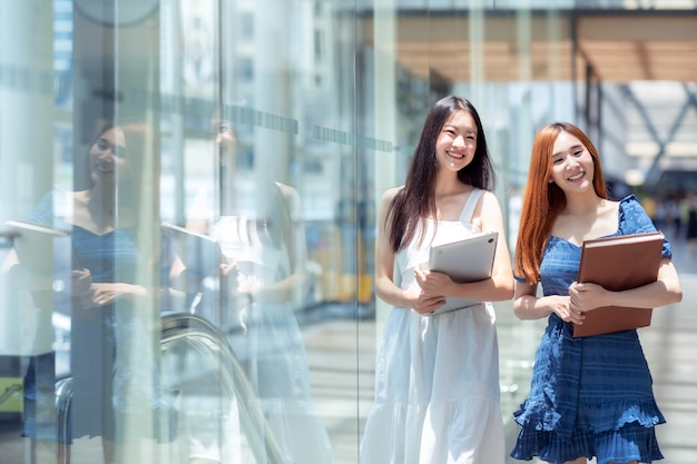 彼女の大学で図書館に歩いている2つのアジアの学生