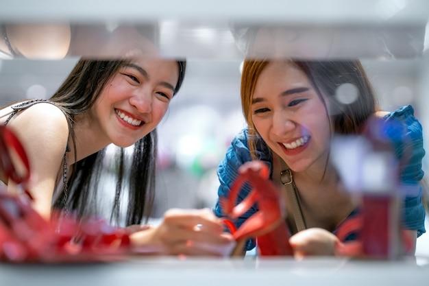 エレガントな靴を示す2つの驚きのアジアの女の子