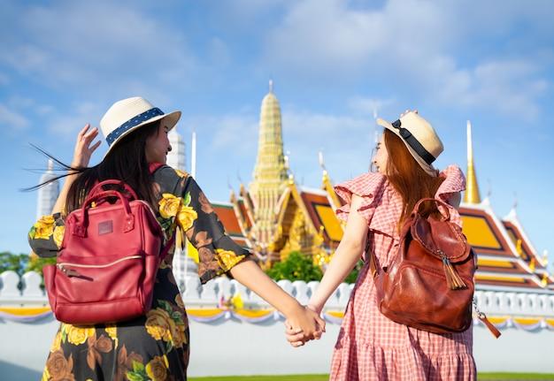 グランドパレスとワットプラケオで旅行し、実行している2つのアジアのガールフレンド