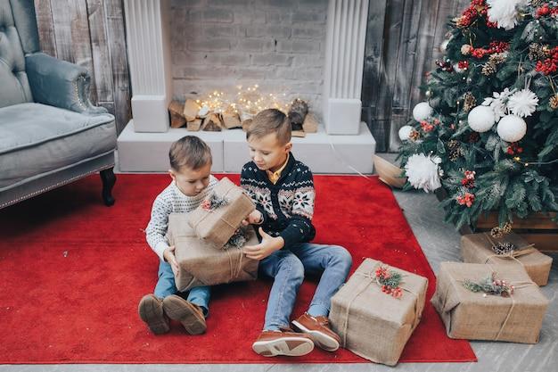 2人の魅力的な男の子がクリスマスプレゼントボックスを開く