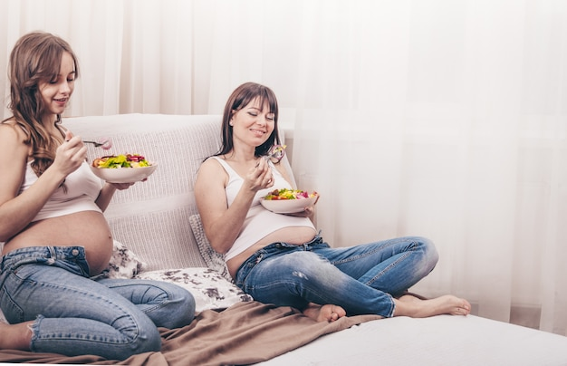 マタニティコンセプト、自宅で新鮮なサラダを食べる2人の妊娠中の女性