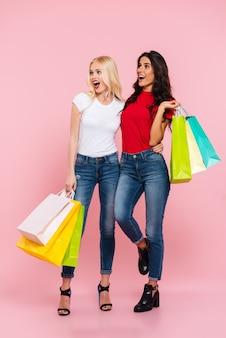 ピンクの上に目をそらしている手でパッケージを持つ2人のショックを受けた幸せな女性の全身画像