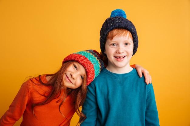 暖かい帽子をかぶっている2人の幸せな小さな子供。