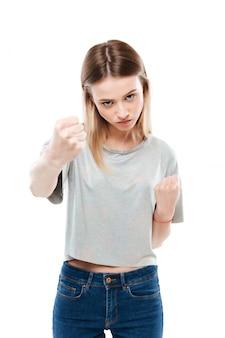 2つの拳を示す深刻な攻撃的な女性の肖像画