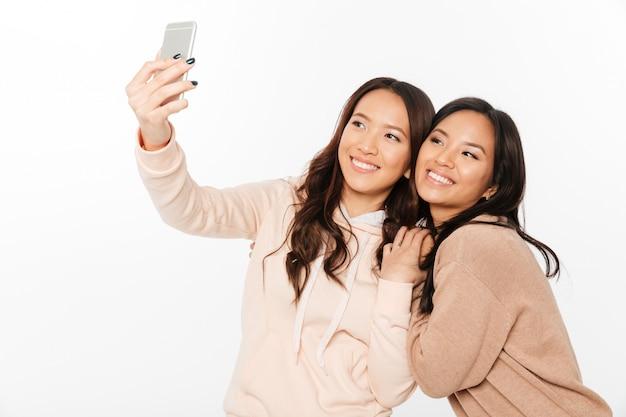 2つのアジアの陽気な肯定的な女性姉妹