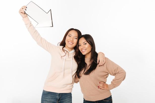 矢印を保持している2つのアジアの正の女性姉妹。