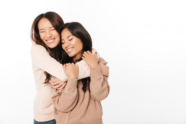2 азиатских милых сестры дам стоя изолированный