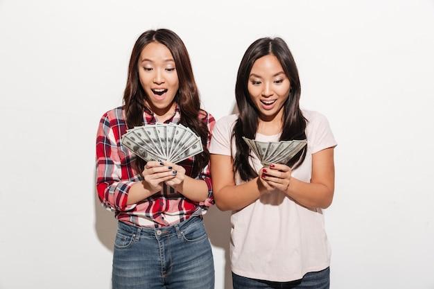 2 азиатских довольно сотрясенных милых дамы держа деньги.