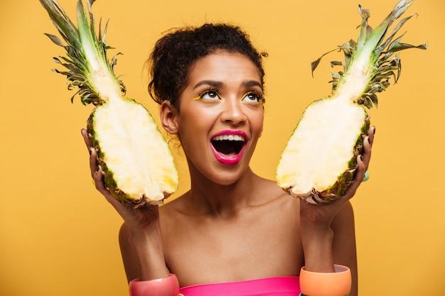 黄色の壁を越えて上向きに見て、分離された新鮮な食欲をそそるパイナップルの2つの部分を保持しているカラフルなメイクと空腹のムラートの女性