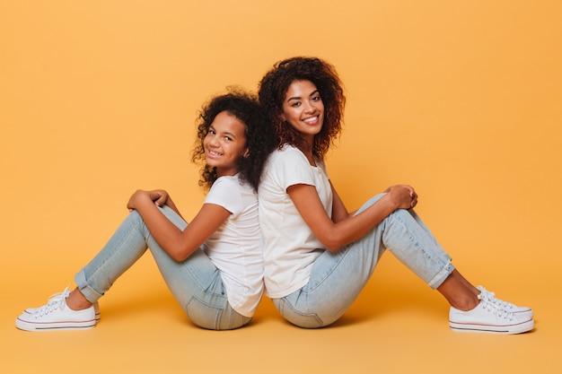 背中合わせに座っている2人のアフリカの姉妹の全長