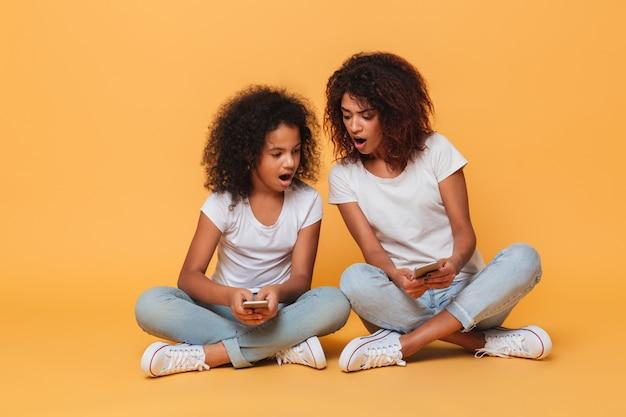 2つの興奮したアフロアメリカンの姉妹の肖像