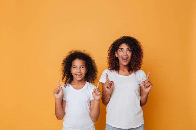 指を指している2つのうれしそうなアフロアメリカンの姉妹の肖像