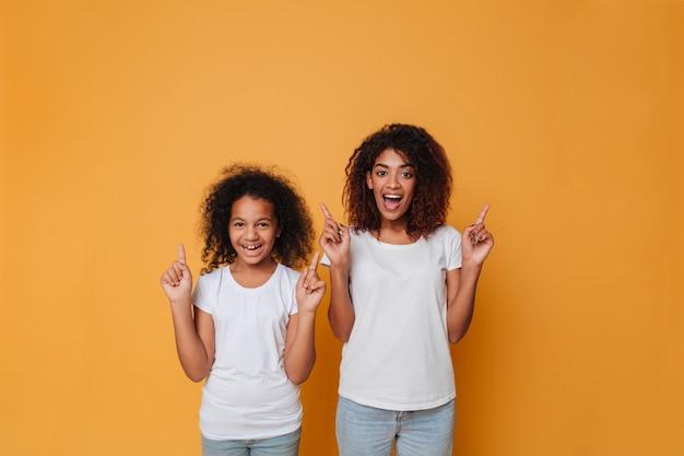 指を指している2人の陽気なアフロアメリカンの姉妹の肖像