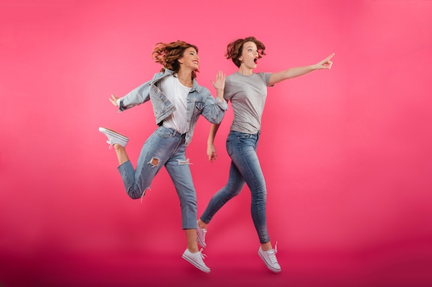 2人の感情的な女性の友人がジャンプして指しています。