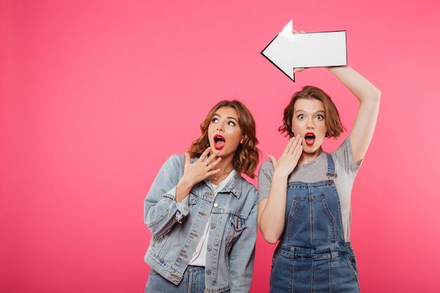 矢印を保持している2人の女性の友人に衝撃を与えた。
