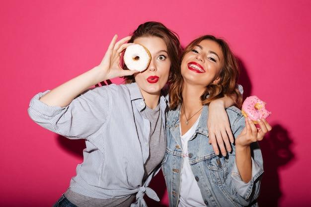 ドーナツを食べている驚くべき2人の女性の友人