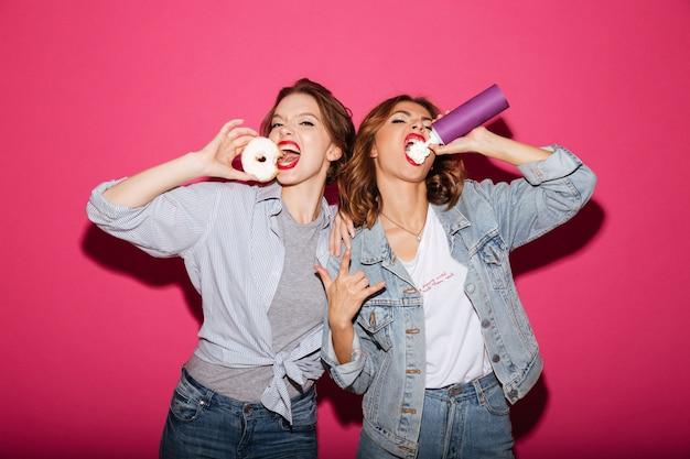 お菓子を食べる驚くべき2人の女性の友人