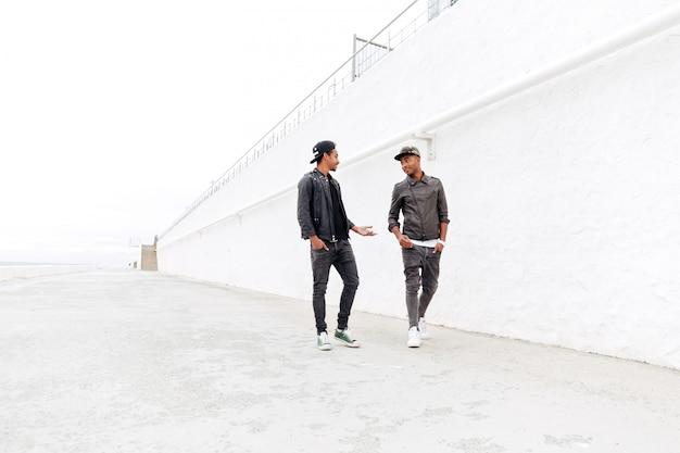 歩いているハンサムな2人の若いアフリカ人男性の友人
