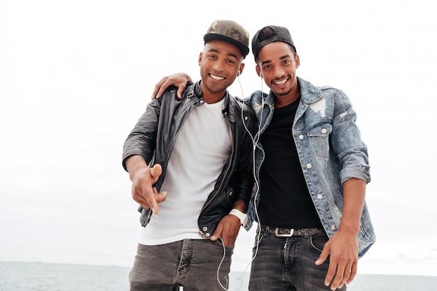 Счастливые 2 молодых африканских друз друзей слушая музыка.