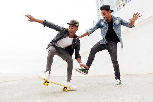 歩いて感情的な2人の若いアフリカ人男性の友人