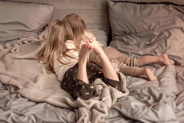寝室のベッドの上に敷設する2人の女の子