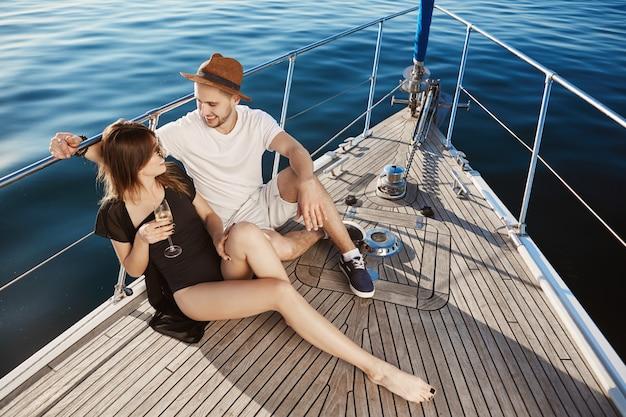 2人の若い魅力的なヨーロッパ人がヨットの船首に座って、休暇中にいじめ、いちゃつく。素敵なカップルは、これを今日とそのすべての明日について共有したいと考えています。一緒に彼らは気楽に感じます。