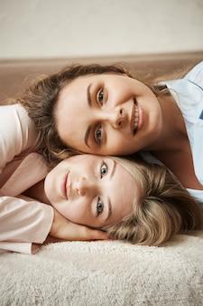 姉妹のような感じの親密な関係を持つ2人の女の子。ソファに横になって広く笑っている見栄えの良い女性の垂直方向のショット。彼女の親友の頭の上に横たわる魅力的な縮れ毛の友人