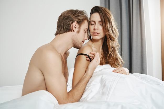 ハンサムなひげを生やしたボーイフレンドの寝室のショットは、毛布の下で裸である間にガールフレンドの肩にキスします。愛を表現する朝の前戯を持つ関係の情熱的な2人