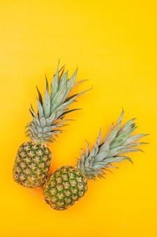 2 мясистых ананаса на желтом цвете, взгляд сверху.