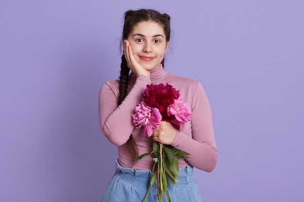 牡丹の花束を手で押し、ライラックの壁にポーズをとる魅力的なかわいい女の子、頬に手のひらをつけた魅力的な女性、心地よい外観の女性と2つのおさげ髪。