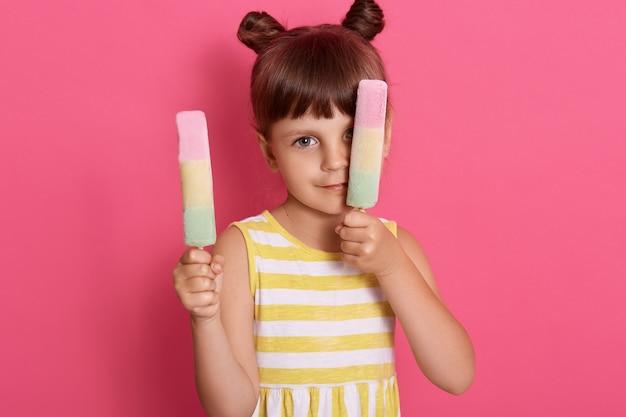 ピンクの壁の上に孤立したポーズの両手でウォーターアイスクリームを持つ少女。片方の目をシャーベットで覆い、2つの髪のパンを持つ面白い女の子と思いやりのあるアイスクリーム。