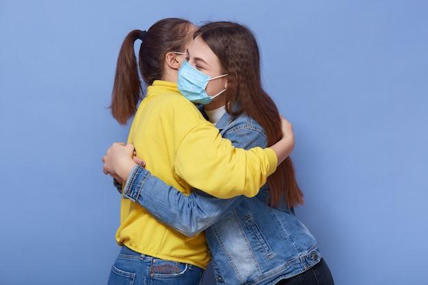 カジュアルな服装と健康マスクを身に着けている2人の女性の肖像画を間近します。