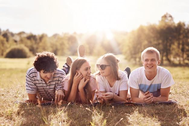 ボーイフレンドの近くの緑の芝生でお腹の上に横たわっている間、2人の女性の仲間は楽しい話をしています