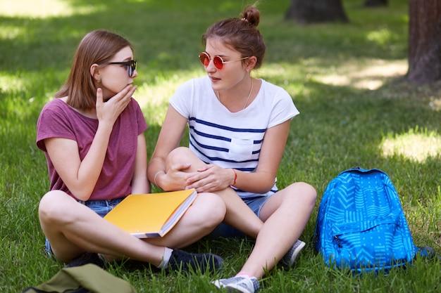 2人の女性の仲間は、会話をしながらお互いを見つめ、足を組んで座って、大学でニュースについて話し合い、本を持ち、緑の芝生に座って心地よく感じます。人とライフスタイルのコンセプト