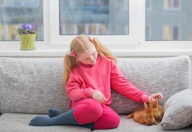 屋内2匹のウサギと笑顔の女の子