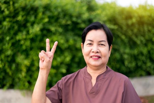 Зрелая азиатская женщина стоя и показывая 2 пальца на общественном парке, счастливый и усмехаясь, концепция страхования старшей заботы